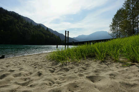 A grassy and sandy beach next to a glacier fed body of water.