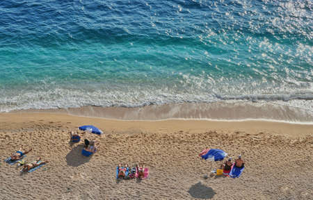 vacationer: Vacationers - tourists enjoying the sun and sea on the beach in Turkey Stock Photo