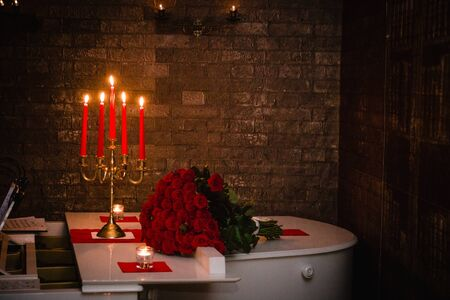 Candles and a bouquet of 100 red roses on a white piano.