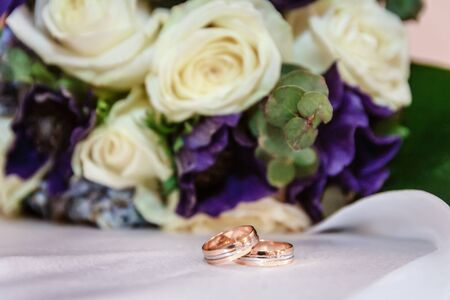 Wedding rings against the background of a bouquet of roses