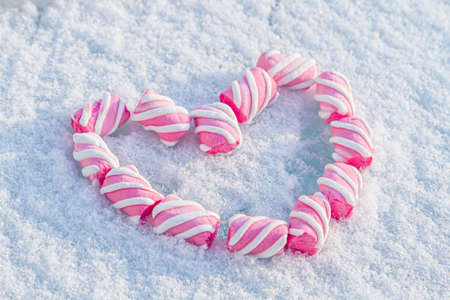 Heart made of marshmallows in the snow. Red heart on a white background. Valentine's Day. Sweets as a gift. Romantic background for Valentine's Day