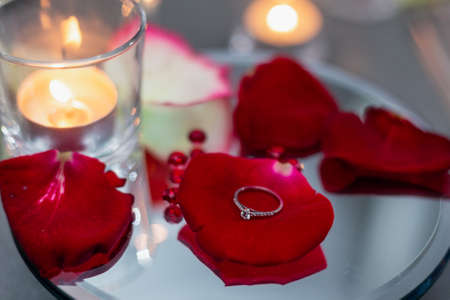 Wedding ring lies on red rose petals on the background of candles. Marriage proposal. Romantic atmosphere Imagens