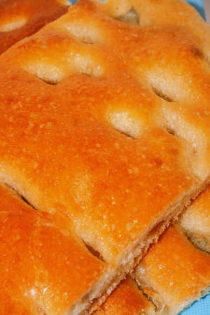 surface: Focaccia is a typical kind of salty bread baked in Genoa, Italy. We  's crispy and salty surface are spread with high quality olive oil. Delicious. Stock Photo
