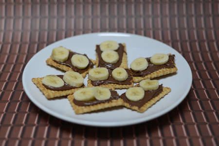 nutella: Biscuits with nutella. Chocolate and banana on a background texture.