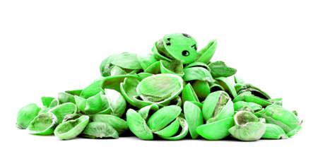 phantasy: Funny smiling green dinosaur pistachio, on heap of nutshells