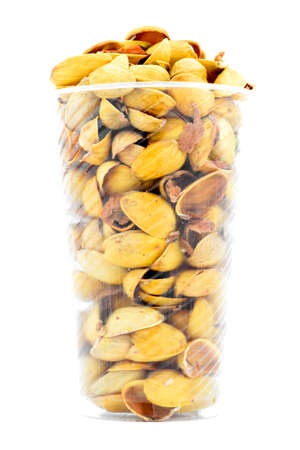 nutshell: Yellow pistachio nutshell heap in plastic cup, isolated on white