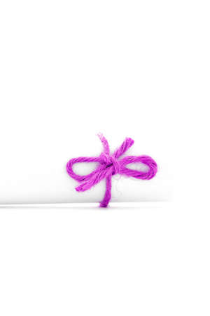 missive: Handmade pink cord node tied on white letter scroll, isolated