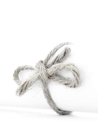 missive: Handmade natural string bow tied on white paper scroll, isolated Stock Photo