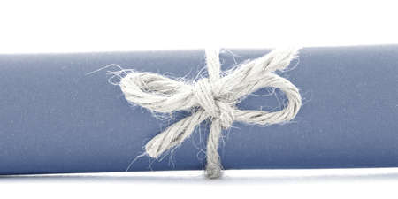 missive: Handmade natural cord knot tied on blue paper roll, isolated