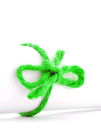 missive: Handmade green rope node tied on white paper scroll, isolated