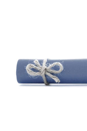 natural rope: Handmade natural rope knot tied on blue letter scroll, isolated Stock Photo