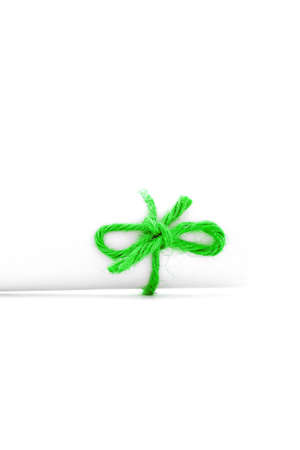 missive: Handmade green cord knot tied on white paper package, isolated