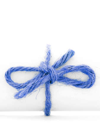 node: Handmade blue rope node tied on white message roll, isolated
