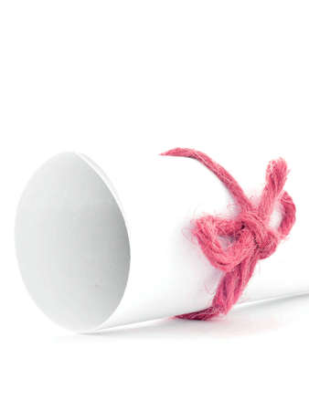 node: Handmade red cord node tied on white paper scroll, isolated Stock Photo