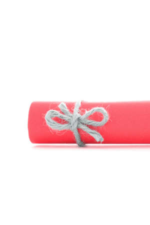 natural rope: Handmade natural rope node tied on red paper scroll, isolated