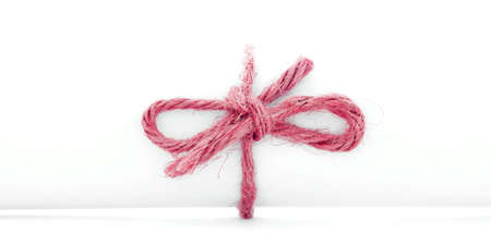 missive: Handmade red cord knot tied on white message package, isolated Stock Photo