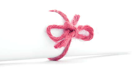 missive: Handmade red rope knot tied on white letter package, isolated