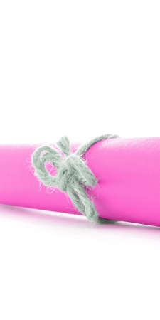 missive: Handmade natural rope node tied on pink paper roll, isolated