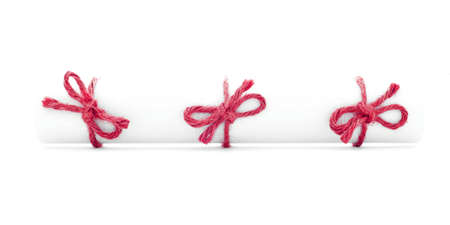 missive: White letter tube tied with rope, three red bows, isolated Stock Photo