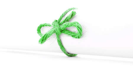missive: Handmade green rope knot tied on white paper scroll, isolated Stock Photo