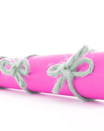 missive: Natural handmade cord knots tied on pink message scroll, isolated