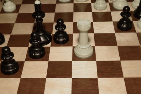 Wooden chessboard with white chessmen as a game background