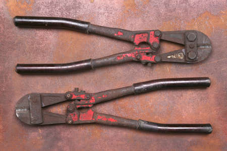 cutters: Wire cutters on the front and back and rust background.