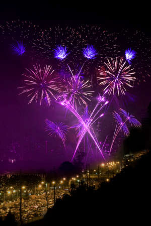 Purple fireworks light up the night sky. Stock Photo
