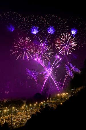 next year: Purple fireworks light up the night sky. Stock Photo