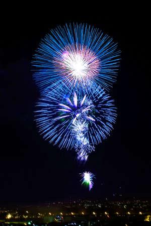 next year: Blue fireworks light up the night sky.