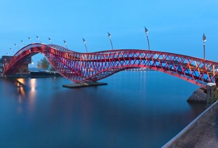 アムステルダム, オランダ - 夜間景観の Python 橋