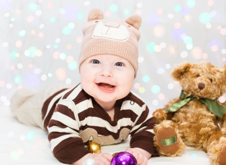 Beautiful little baby in the bear hat with ears, lays with toys and smiles  photo