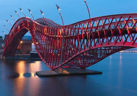 Amsterdam, Nederländerna - 18 oktober 2013 En av två broar i ett komplex, som heter Python Bridge Detta broar är ett exempel på modern arkitektur och design av Amsterdam De har den ovanliga böjda formen och ljust röd färg Stockfoto