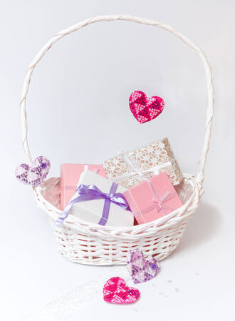 Cute white and pink boxes with bows and ribbons and hearts in pastel colors in white basket on the white background. photo