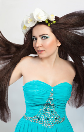 Beautiful Sensual Brunette Girl in Orchid Wreath  Healthy Flying Long Hair, Clear Young Skin photo