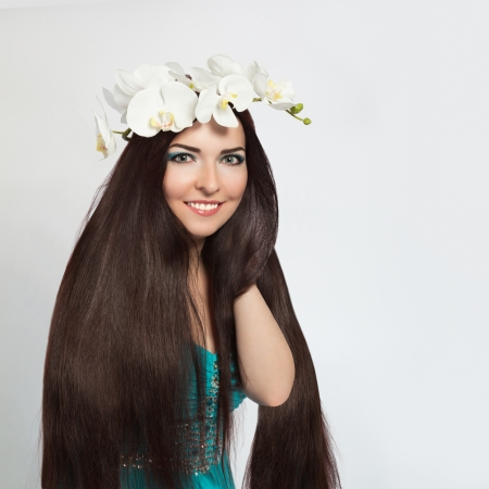 Beautiful Smiling Brunette Girl in Orchid Wreath  Healthy Long Dark Hair, Clear Young Skin, White Teeth  photo