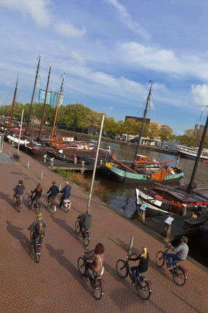 bicycle walk: 16 OCTOBER 2013 AMSTERDAM, NETHERLANDS The group of tourists makes bicycle walk along quay with the moored boats museums in the center of Amsterdam