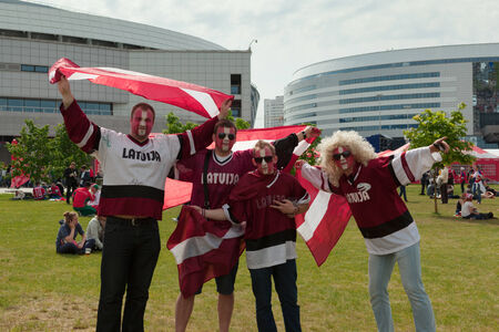 public spirit: MINSK, BELARUS - May 17, 2014  ICE HOCKEY WORLD CHAMPIONSHIP, MINSK-ARENA, The hockey fans from Latvia with national flags in the uniform of a national team of Latvia Editorial
