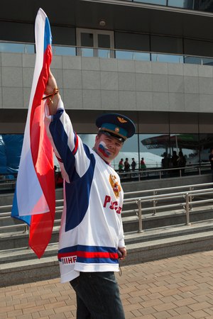 public spirit: MINSK, BELARUS - May 17, 2014  ICE HOCKEY WORLD CHAMPIONSHIP, MINSK-ARENA, The hockey fan from Russia with national flag in the uniform of a national team of Russian Federation Editorial