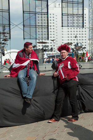 public spirit: MINSK, BELARUS - May 17, 2014: ICE HOCKEY WORLD CHAMPIONSHIP, MINSK-ARENA, The hockey fans from Latvia with national flags in uniform upset after defeating Russian Editorial
