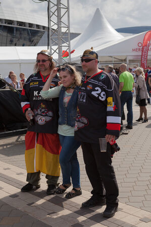 public spirit: MINSK, BELARUS - May 17, 2014  ICE HOCKEY WORLD CHAMPIONSHIP, MINSK-ARENA, The hockey fans from Germany with national flags in the in the uniform of a national team of Germany