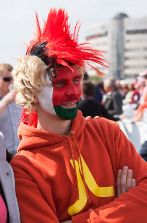 public spirit: MINSK, BELARUS - May 17, 2014  ICE HOCKEY WORLD CHAMPIONSHIP, MINSK-ARENA, The hockey fan from Belarus with national flag on the faсe in bright colored wig Editorial