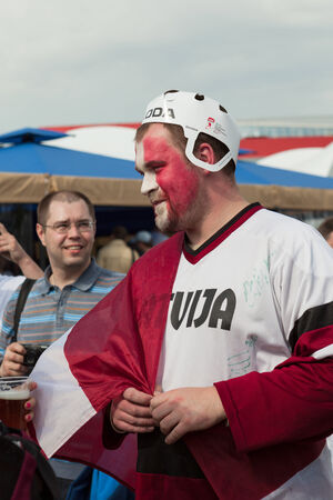 public spirit: MINSK, BELARUS - May 17, 2014  ICE HOCKEY WORLD CHAMPIONSHIP, MINSK-ARENA, The hockey fan from Latvia with national flag in the uniform of a national team of Latvia