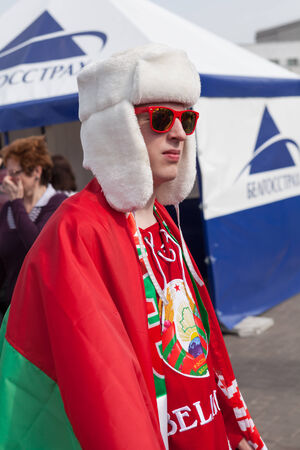 public spirit: MINSK, BELARUS - May 17, 2014  ICE HOCKEY WORLD CHAMPIONSHIP, MINSK-ARENA, The hockey fan from Belarus in white hat  ushanka  with national flag in the uniform of national team of Belarus