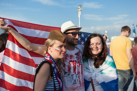 public spirit: MINSK, BELARUS - May 18, 2014  ICE HOCKEY WORLD CHAMPIONSHIP, MINSK-ARENA, The hockey fans from Russia and USA with national accessories and USA flag Editorial