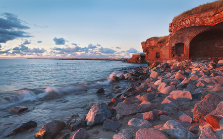 shined: Ruins of the old brick fortress shined with solar beams, on the shore of Baltic sea - sunset landscape Stock Photo