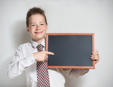specifies: The nice smiling boy teenager in a white shirt and a tie on a grey background specifies a finger in an empty black board for a chalk Stock Photo