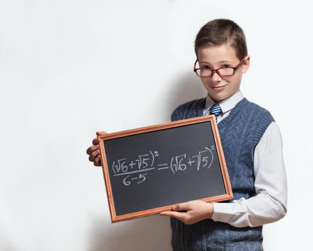 The cute smart schoolboy teenager in a glasses shows the black chalkboard with the mathematical equation photo