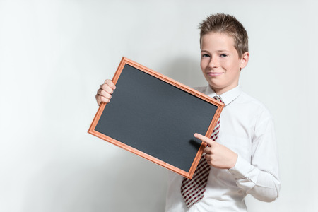 specifies: The nice smiling boy teenager in a white shirt and a tie on a grey specifies a finger in an empty black chalkboard