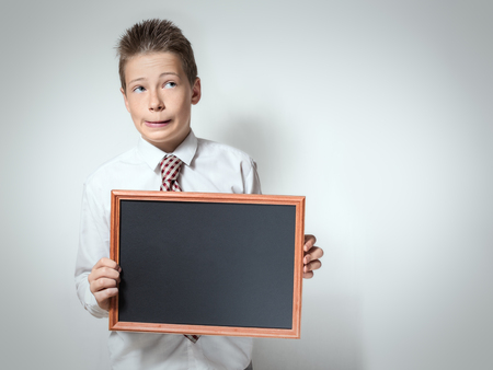leer: The cute funny schoolboy teenager in a white shirt holds the black empty chalkboard with place for text